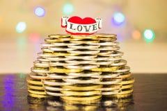 Pyramide des pièces de monnaie avec l'amour d'inscription sur le dessus Le fond lumineux trouble allume la table Images libres de droits