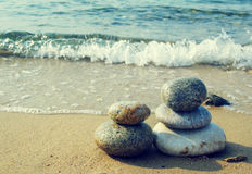 Pyramide des pierres de mer contre la mer Photographie stock