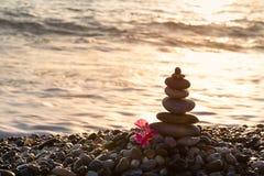 Pyramide des pierres et fleur rouge sur le bord de la mer Photo stock
