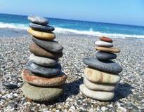 Pyramide des pierres sur la plage contre la mer et le ciel Photographie stock