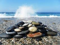 Pyramide des pierres sur la plage contre la mer et le ciel Photo libre de droits