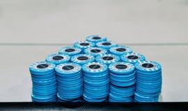 Pyramide, die aus Stapel von blauen Pokerchips auf Tabelle mit Kopienraum besteht stockfotos