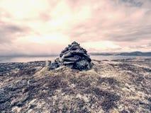Pyramide en pierre équilibré sur la crête de la montagne au-dessus de la baie de mer Photographie stock libre de droits