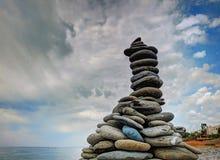 Pyramide en pierre sur la côte de pierre de mer près à la plage de sable de cerf-volant sur l'île tropicale Vacances de vacances  Photos libres de droits