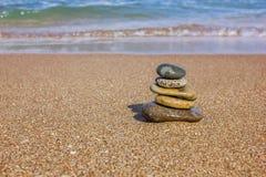 Pyramide von den flachen Steinen auf einem sandigen Strand lizenzfreie stockfotos
