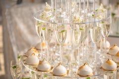 Pyramide von den Gläsern Champagner und Kuchen auf Hochzeitsfest stockfotografie
