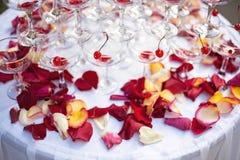 Pyramide von Weingläsern mit Wein oder Champagner und rosafarbene Blumenblätter Lizenzfreie Stockbilder