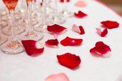Pyramide von Weingläsern mit Wein oder Champagner und rosafarbene Blumenblätter Stockbild
