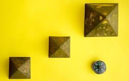 Pyramiden und Kompass auf gelbem Hintergrund Stockbild