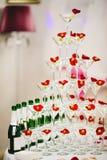 Pyramidengläser Champagner mit Oliven und den rosafarbenen Blumenblättern lizenzfreie stockfotos