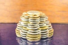 Pyramiderna av guld- och silvermynt på brun suddig bakgrund Affärsidéfinans Arkivfoto