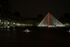 Pyramides et fontaine de musée de Louvre pendant la nuit Images libres de droits