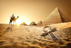 Pyramids and ankh. Bedouin on camel near pyramids and ankh in desert Stock Image