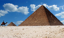 Pyramids of Giza,  Egypt. A man riding a camel walks past the iconic pyramids of Giza in Egypt Royalty Free Stock Photos