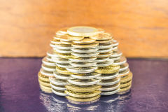The pyramids of gold and silver coins on brown blurred background. Business concept finance. Stock Photo