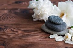 Pyramids of gray zen stones with White flowers, green leaves on wooden background. Concept of harmony, balance and meditation,. Pyramids of gray zen stones stock images