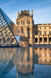 Pyramids and the Luvre reflected in fountain Stock Images