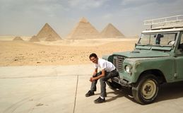 Pyramids Safari. Egyptian young man sitting on the pumper of a four wheel drive with the great pyramids of Giza on the background Royalty Free Stock Photo