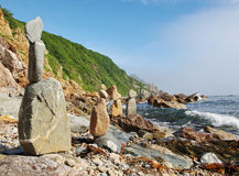 Pyramids of stones on rocky coast. Royalty Free Stock Photos
