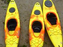 Three yellow kayaks lying on mud Royalty Free Stock Photography