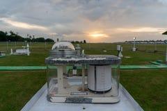 Pyranograph på meteorologifältet med grönt gräs och när solnedgång under molnig himmel royaltyfri fotografi