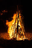 Pyre burning on the beach. A pyre burning in the night on a beach during summer holidays. Vertical ratio Stock Photo