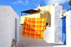 Pyrgos, Santorini/Grecia: Un copriletto arancio e giallo, appendente per asciugarsi su un tetto nel villaggio di Pyrgos fotografia stock