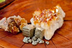 Pyrite, Citrine and Honey Calcite crystals - on wood tree stump Royalty Free Stock Photos