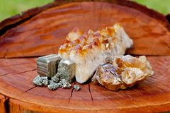 Pyrite, Citrine and Honey Calcite crystals - on wood tree stump Royalty Free Stock Images