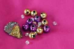 Pyrite rock with beads. On a bright pink background Stock Images