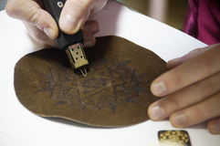 Pyrography on a skin. Photo of a process of a pyrography on a skin by using a device for a pyrography Stock Image