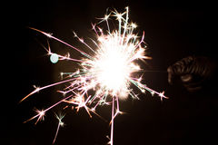 Pyrotechnic sparkler. Lighting equipment for New Year and Christmas. A sparkler is a type of hand-held firework equipment that burns slowly while emitting Stock Images