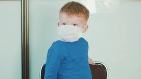 Pys ett barn i en medicinsk maskering i sjukhuset Begreppet av en epidemi, influensa, skydd från sjukdom stock video