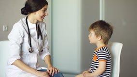 Pys för doktor för ung kvinna talande och lyssna med stetoskopet i medicinskt kontor Royaltyfri Bild