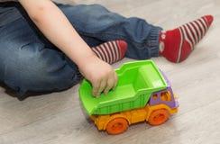 Pys hand som rymmer en leksakbil Arkivfoton