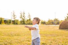 Pys i bygden Litet barn som spelar aktiva lekar utomhus Barndom som är bekymmerslös, barns lekar, pojke som är ny Royaltyfri Fotografi