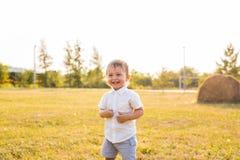 Pys i bygden Litet barn som spelar aktiva lekar utomhus Barndom som är bekymmerslös, barns lekar, pojke som är ny Royaltyfri Bild