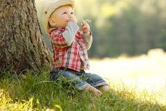 Pys i en cowboyhatt som spelar på naturen Royaltyfri Foto