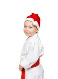 Pys i en kimono med ett rött bälte och lock av Santa Claus Royaltyfria Foton