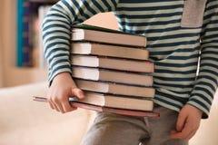 Pys i en randig skjorta som rymmer en hög av böcker Utbildnings- och kunskapsbegrepp Läs- barn tillbaka skola till arkivfoto
