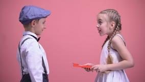 Pys i formella kläder som framlägger födelsedaggåvakortet till den lyckliga förvånade flickan stock video
