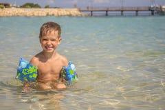 Pys i havet med uppblåsbara över-muffar fotografering för bildbyråer