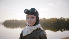 Pys i pilot- dräkt för tappning med halsduken och exponeringsglas som ser kameran som ler nära lugna solnedgångsjöultrarapid arkivfilmer