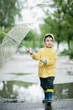 Pys i regnrocken och gummistöveler som spelar i pöl Lycklig liten unge med paraplyet royaltyfri foto