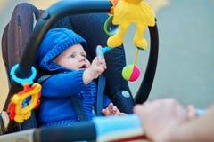 Pys i sittvagnen som spelar med leksaker Fotografering för Bildbyråer