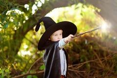 Pys i spetsig hatt och svarta kappan som spelar med trollspöet utomhus liten trollkarl royaltyfri bild