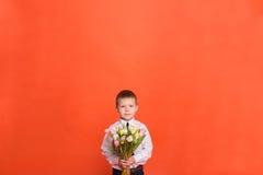 Pys med blommor som poserar i studion på en röd bakgrund Arkivfoto