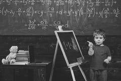 Pys med den listiga framsidan som framme står av grönt bräde Elev som pekar på den svart tavlan Barn som lär aritmetisk arkivbilder