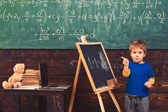 Pys med den listiga framsidan som framme står av grönt bräde Elev som pekar på den svart tavlan Barn som lär aritmetisk royaltyfria foton