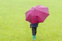 Pys med det röda paraplyet i regnet tillbaka sikt fotografering för bildbyråer